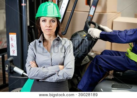 Portrait of confident female supervisor with man driving forklift in warehouse