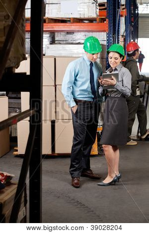 Young female supervisor and colleague using digital tablet at warehouse