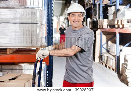 Portrait of warehouse worker pushing handtruck with cardboard boxes at warehouse