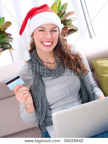 Christmas Online Shopping. Happy Smiling Woman Using Credit Card to Internet Shop. Young Girl with laptop and credit card buying online. Christmas and New Year Gifts. e-shopping