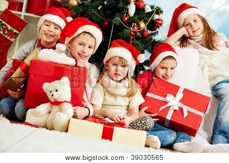 Group of adorable kids in Santa caps looking at camera while sitting by xmas tree