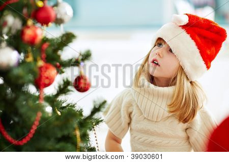 Group of adorable girl in Santa caps looking at xmas tree