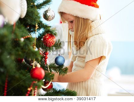Group of adorable girl in Santa caps decorating xmas tree