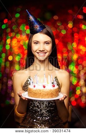 Portrait of joyful girl with cake looking at camera at birthday party