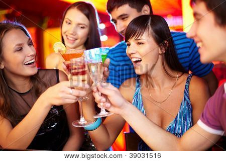 Portrait of joyful friends toasting at birthday party with focus on two happy girls