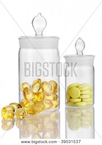 Capsules and pills in receptacles isolated on white