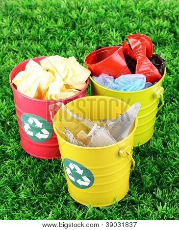 Recycling bins on green grass