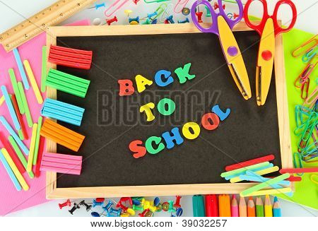 Small chalkboard with school supplies on white background. Back to School