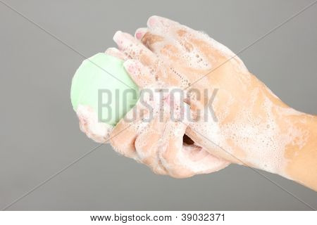 Woman's hands in soapsuds, on gray background close-up