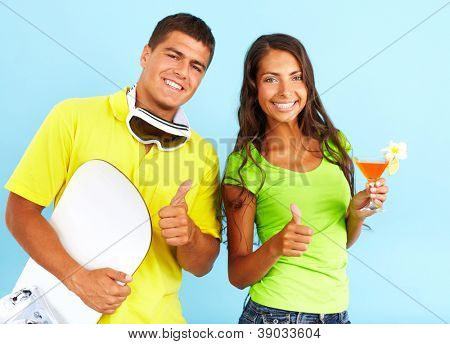 Portrait of happy couple with cocktail and skateboard showing thumbs up and looking at camera