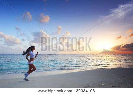 Beautiful young woman in white sportswear running on beach