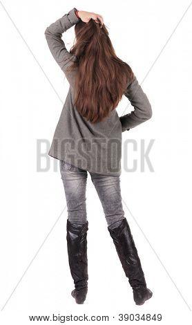 volta a vista da bela jovem de pé.  menina morena de jeans e casaco assistindo;. Vista traseira