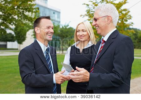 Three happy business partner people talking outside