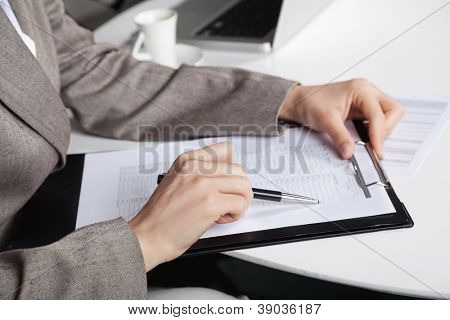 Hand of a businesswoman at her desk with a pen and a clipboard