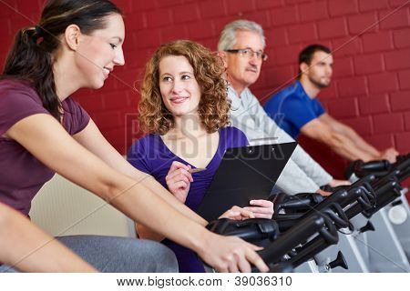 Female fitness trainer helping woman on spinning bike in fitness center