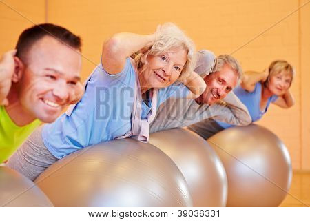 Elderly group doing back exercises in a fitness center