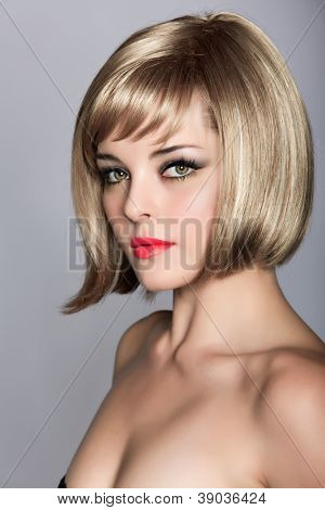 beautiful blond young woman wearing short bob hairstyle on studio background