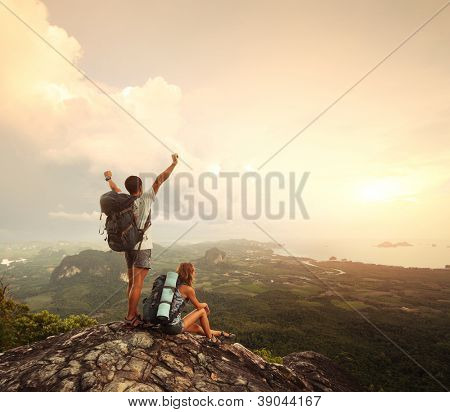 Two hikers with backpacks standing on top of a mountain with great valley view