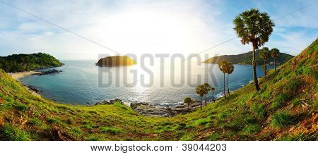 Panorama of tropical coast with beach,  palm trees and island in calm blue sea. Ya Nui beach (left sandy coast) of Phuket. Thailand