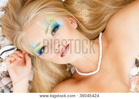 fresh attractive teenager girl mermaid with beautiful make-up lying on beach