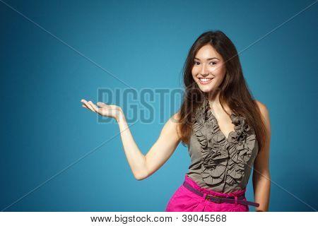 mooie tiener meisje iets met de hand, op blauwe achtergrond weergegeven: