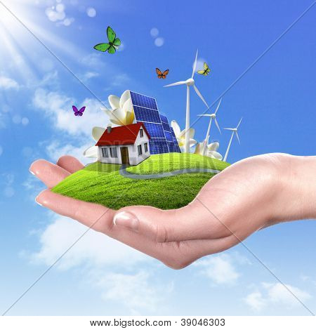 Hands holding a green earth with solar batareis