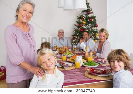 Smiling grandmother and granddaughter standing beside the dinner table at christmas