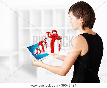 Beautiful young woman looking at modern tablet with present boxes