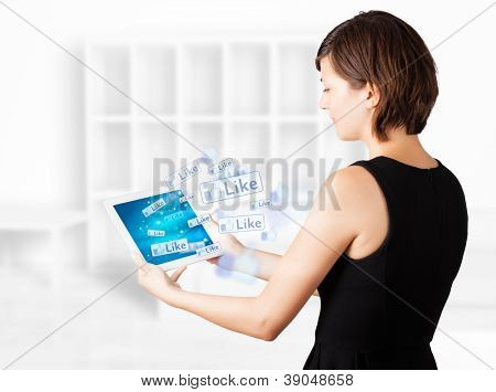 Young Woman looking at modernen Tablet mit social icons
