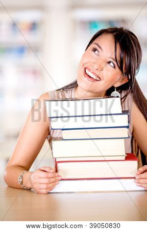 Excited female student looking up thinking at the library