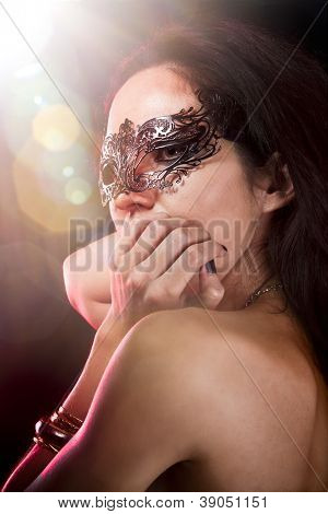 Sexy woman with  venetian mask, red light at background, shine effects