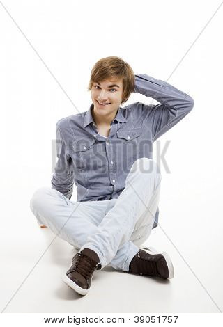 Happy young man sitting on the floor, over a white background