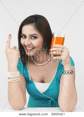 Woman Of Indian Origin Drinking Orange Juice