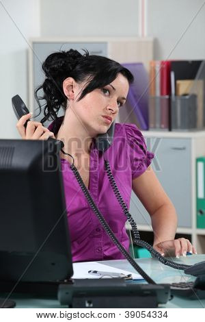 Stressed receptionist taking several calls at once