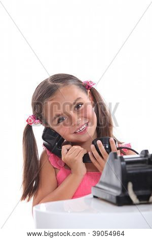 Young girl using an old fashioned black telephone
