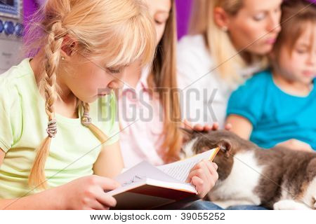 Happy family - mother is reading a book, she and the children are sitting in a kid's room