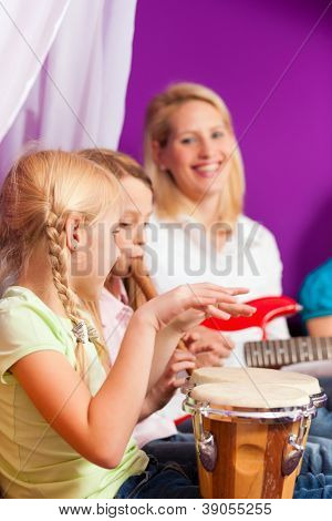 Family - Children and mother - making music, at home, they are practicing playing guitar, bongo and flute as instruments