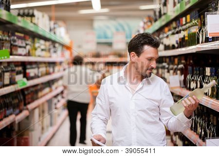 Young man shopping for liquor at supermarket