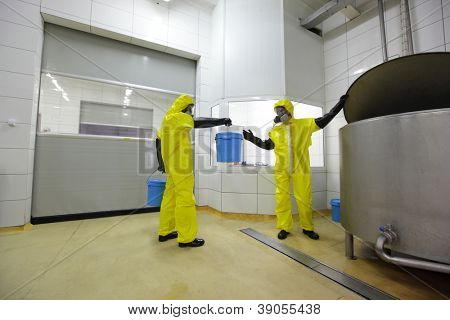 Two professionals fully protected in yellow uniforms,masks,and gloves working  at large industrial process tank in factory.