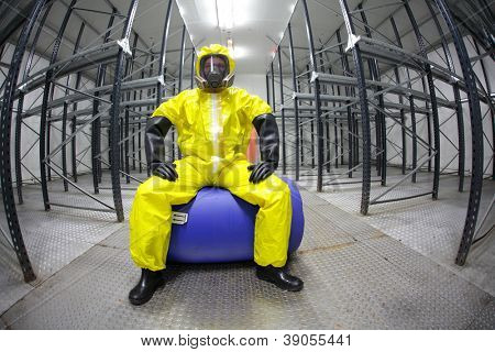 worker in safety - protective uniform,sitting on blue barrel -  portrait