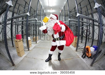 Santa Claus preparing for Christmas,selecting presents  in empty storehouse, fish-eye photo