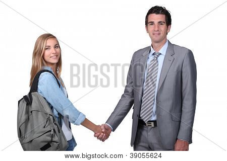 Young student shaking hands with a man in a suit