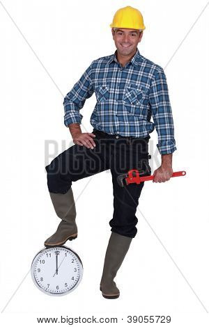 Happy laborer leaning on a clock, studio shot