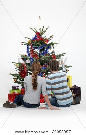 Couple sat by Christmas tree