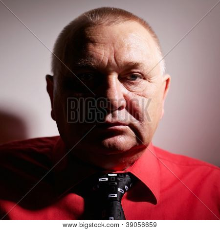 Dramatic close up portrait of middle aged business man in red shirt and tie