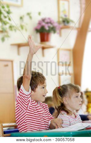 Alunos de ensino fundamental, levantando as mãos