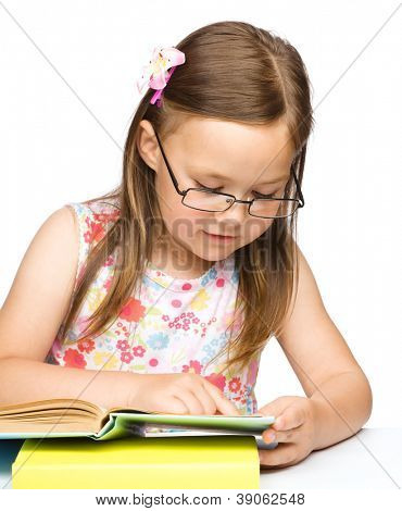 Cute little girl with book wearing glasses, isolated over white