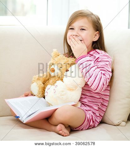 Little girl is reading a book for her teddy bears while sitting on white couch