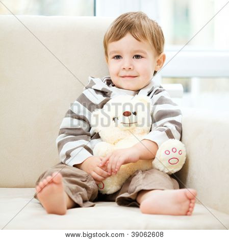 Little boy is holding his teddy bear while sitting on a sofa
