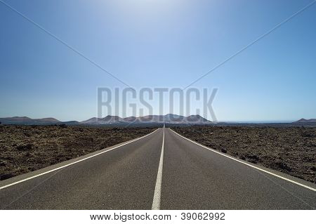 Empty And Straight Road Through The Lava Fields On The Canary Islands, Lanzarote.